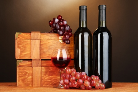Wooden cases with wine bottles on wooden table on brown background Stock Photo - 17046838