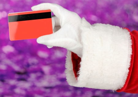 Santa Claus hand holding red credit card on purple background Stock Photo - 17046831