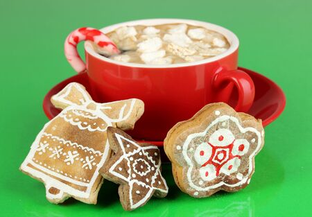 Cup of coffee with Christmas sweetness on green background photo