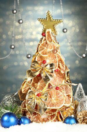 beautiful christmas tree of dry lemons with decor, on shine blue background photo