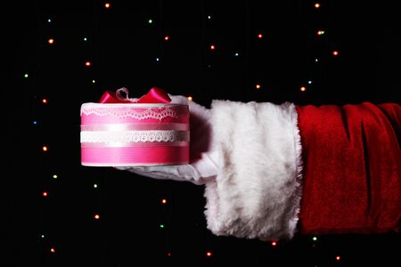 Santa Claus hand holding gift box on bright background Stock Photo - 17053888