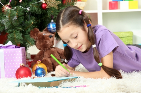 Little girl writing letter to Santa near christmas tree Stock Photo - 17129350