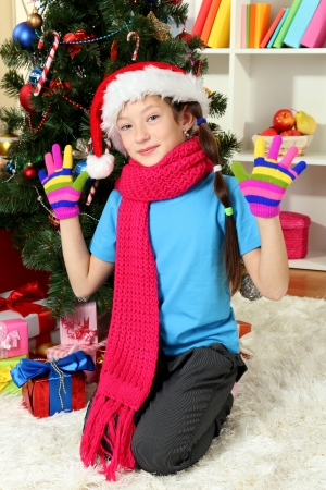 Little girl with pink scarf and multicolor gloves sitting near christmas tree photo