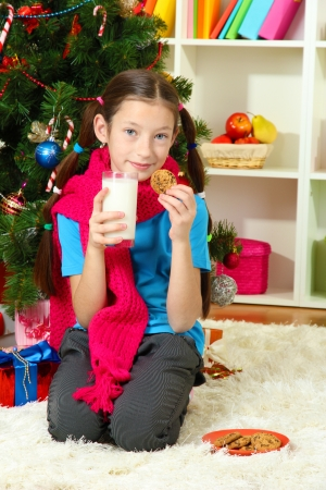 Little girl with pink scarf and glass of milk sitting near christmas tree Stock Photo - 17129499