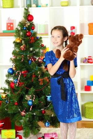Little girl holding toy near christmas tree Stock Photo - 17054730