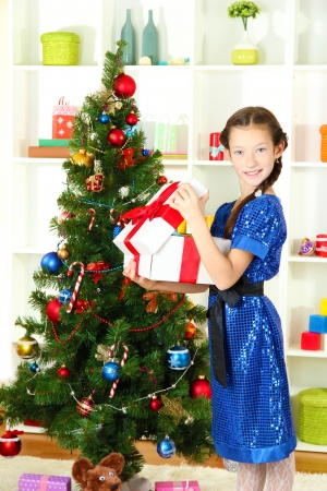 Little girl holding gift box near christmas tree Stock Photo - 17129346