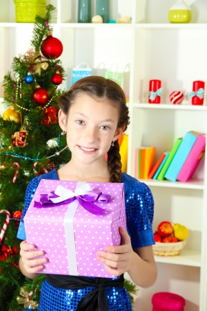 Little girl holding gift box near christmas tree Stock Photo - 17129496