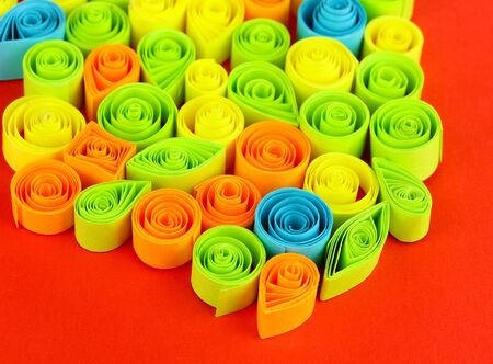 quilling: Colorful quilling on red background close-up