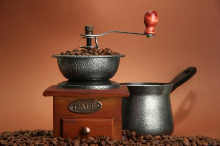 coffee pot: Coffee grinder, turk and coffee beans on brown background Stock Photo