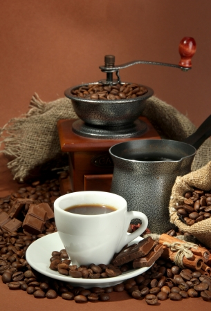 cup of coffee, grinder, turk and coffee beans on brown background Stock Photo - 17054408