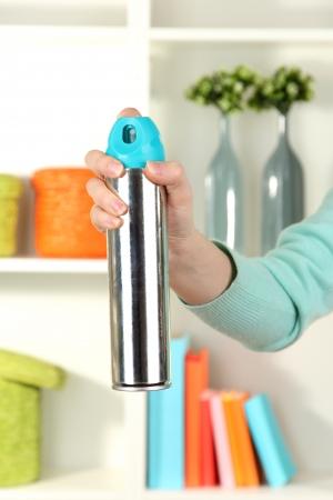 Sprayed air freshener in hand on white shelves background Stock Photo - 17053864