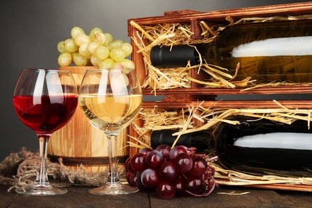 cabarnet: Wooden case with wine bottles, barrel, wineglasses and grape on wooden table on grey background