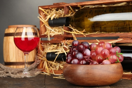 Wooden case with wine bottles, barrel, wineglass and grape on wooden table on grey background Stock Photo - 17054448