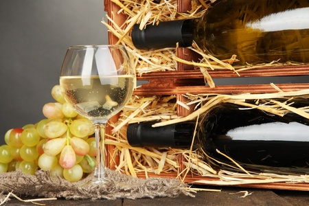 dura: Wooden case with wine bottles, wineglass and grape on wooden table on grey background Stock Photo