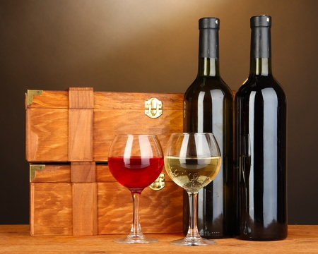 Wooden cases with wine bottles on wooden table on brown background Stock Photo - 17054042