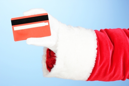 Santa Claus hand holding red credit card on blue background Stock Photo - 17053938
