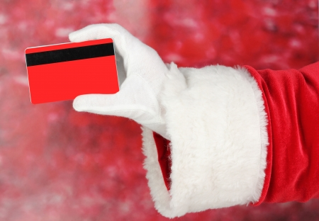 christmas debt: Santa Claus hand holding red credit card on red background