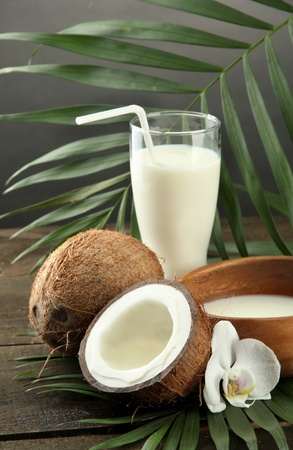 Coconut with glass of milk,  on wooden table, on grey background photo