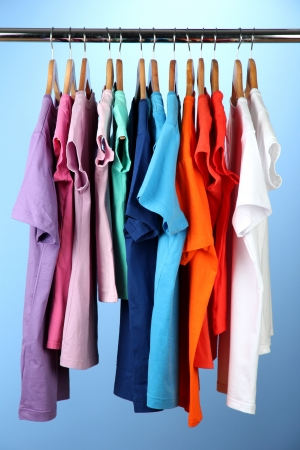 Variety of casual shirts on wooden hangers,on blue background Stock Photo - 17054366