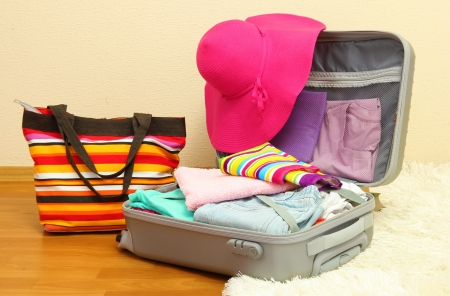 Open silver suitcase with clothing in room Stock Photo - 17054469