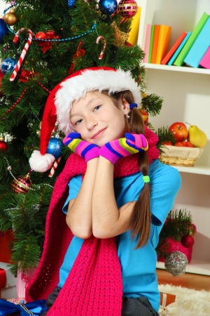 Little girl with pink scarf and multicolor gloves sitting near christmas tree Stock Photo - 17230523