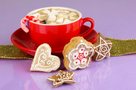 Cup of coffee with Christmas sweetness on purple background photo