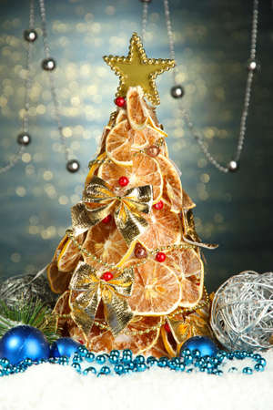 beautiful christmas tree of dry lemons with decor, on shine blue background photo