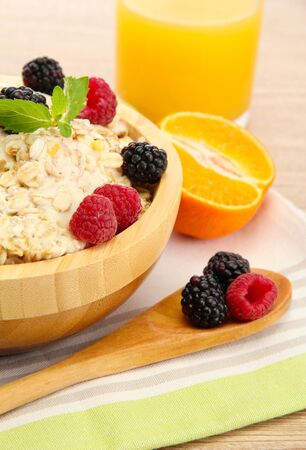 tasty oatmeal with berries and glass of juice, on wooden table photo