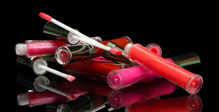 beautiful lip glosses with rose petals, on black background photo