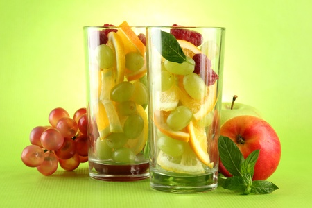 transparent glasses with citrus fruits, on grren background photo