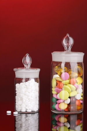 Capsules and pills in receptacles on red background Stock Photo - 17084434