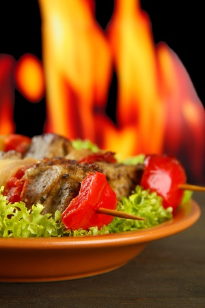 tasty grilled meat and vegetables on plate, on fire background photo