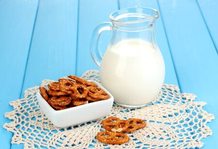 Tasty pretzels in white bowl and milk jug on wooden table close-up Stock Photo - 17086646