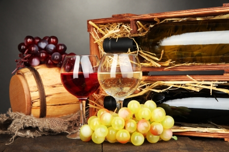 Wooden case with wine bottles, barrel, wineglass and grape on wooden table on grey background Stock Photo - 17086882
