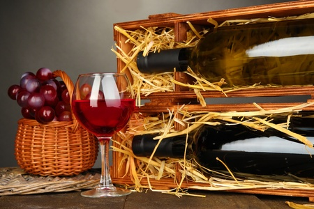 Wooden case with wine bottles, wineglass and grape on wooden table on grey background Stock Photo - 17086759