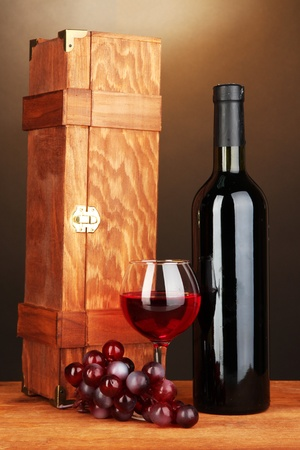 Wooden case with wine bottle on wooden table on brown background photo