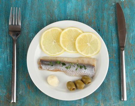 Dish of herring on plate on blue wooden table close-up photo