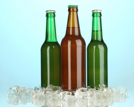 Beer bottles in ice on blue background photo