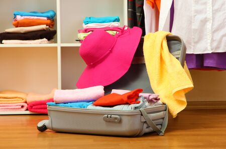 Open silver suitcase with clothing in room Stock Photo - 17086651