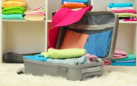 Open silver suitcase with clothing in room Stock Photo - 17086774