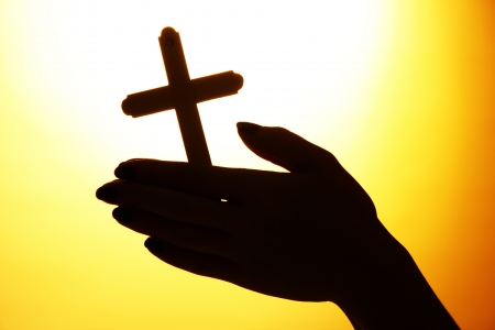 female hands with crucifix, on yellow background photo