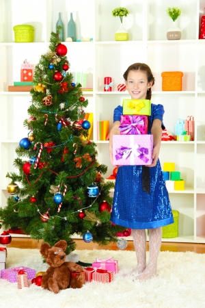 Little girl holding gift box near christmas tree photo