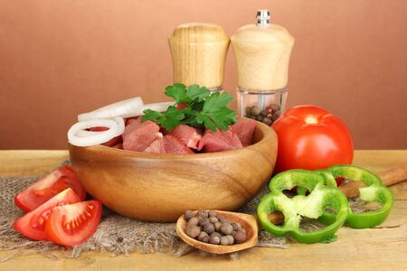 microelements: Raw beef meat with herbs and spices on wooden table on brown background Stock Photo