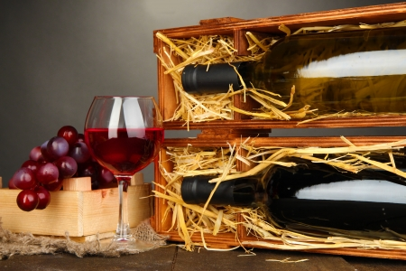bordeau: Wooden case with wine bottles, wineglass and grape on grey background