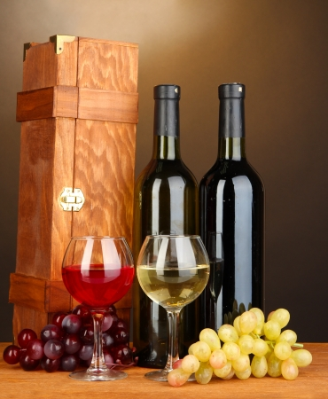 Wooden case with wine bottles on wooden table on brown background photo