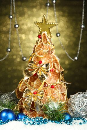beautiful christmas tree of dry lemons with decor, on shine background photo