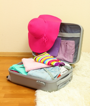 Open silver suitcase with clothing in room Stock Photo - 17111075