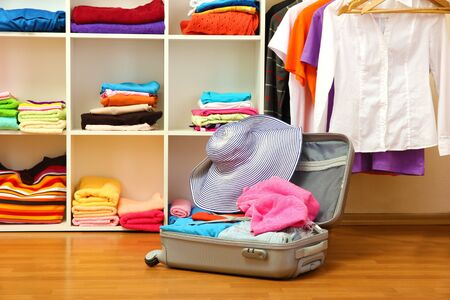 Open silver suitcase with clothing in room Stock Photo - 17111254