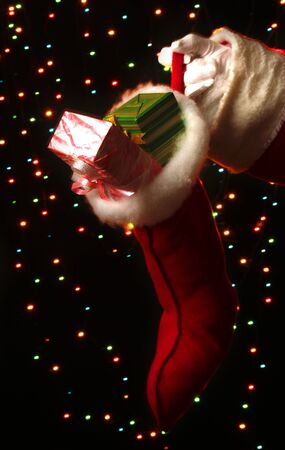 Santa Claus hand holding gifts on bright background Stock Photo - 17133143
