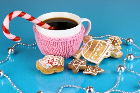 Cup of coffee with Christmas sweetness on blue background photo